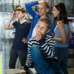 Pensive preteen boy spending time together with his family in escape room stylized as underground shelter, thinking about solving riddles